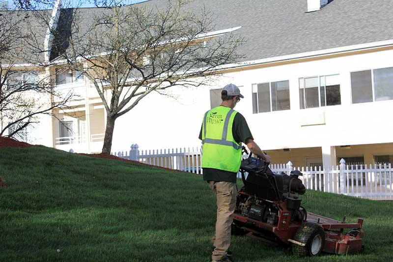 commercial landscaper mowing lawn