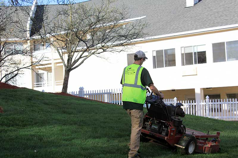 commercial landscaper mowing lawn